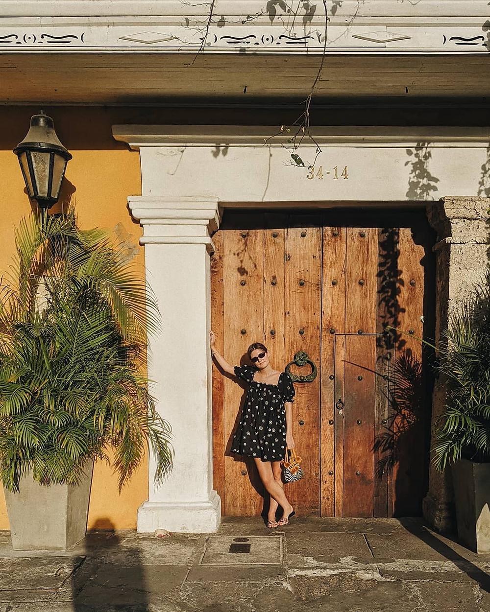 sophie hay stands in front of door on tropical vacation