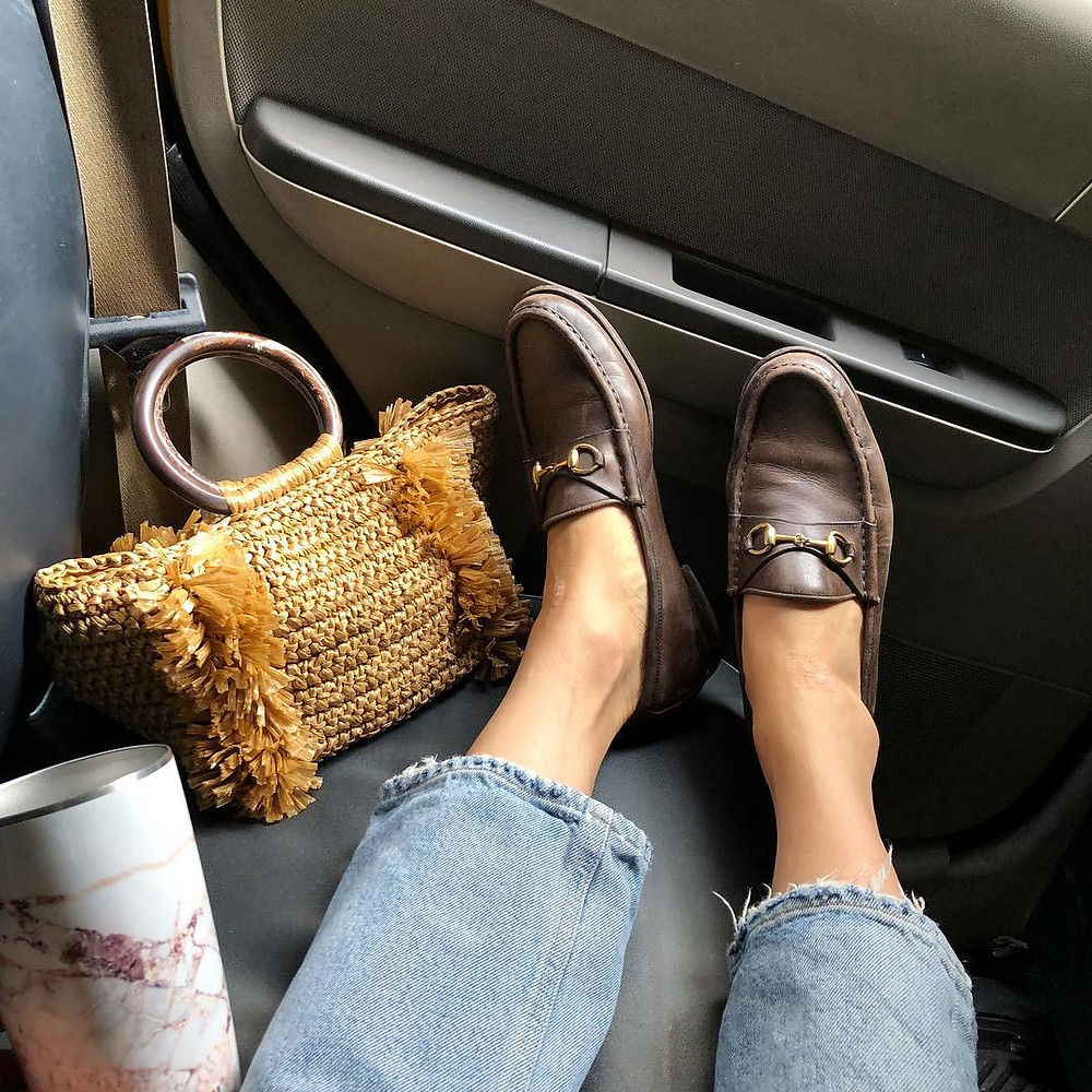 brown loafers with purse in cab