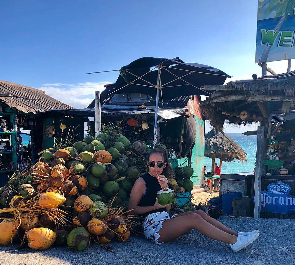 woman lounges in mexico sipping coconut drink