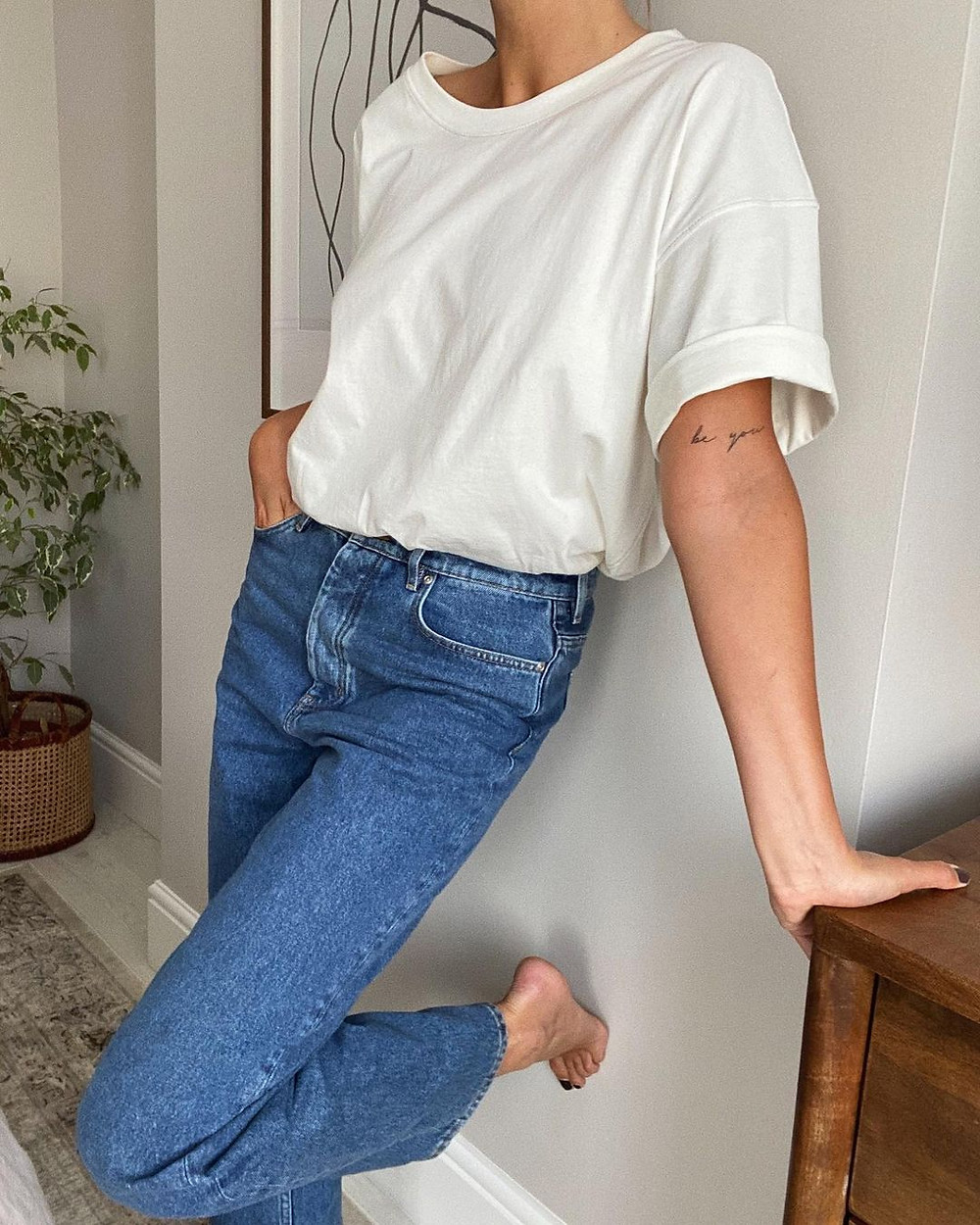 emma hill wears white t-shirt and high waisted blue jeans