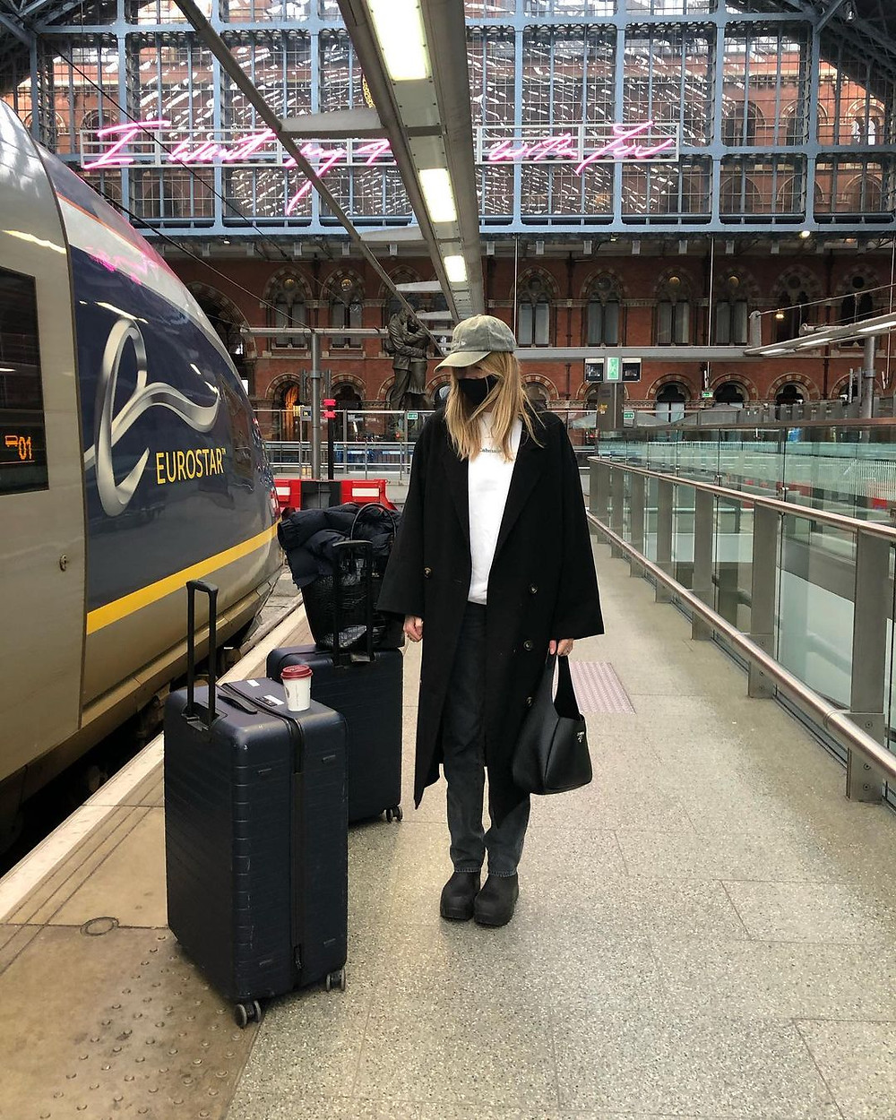 camille charriere stands next to a train with rolling suitcase at a train station while wearing baseball cap, black face mask, black jacket, dark jeans, white t-shirt, and black coat