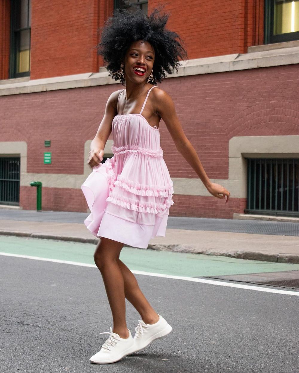 woman in pink dress wears allbirds sneakers