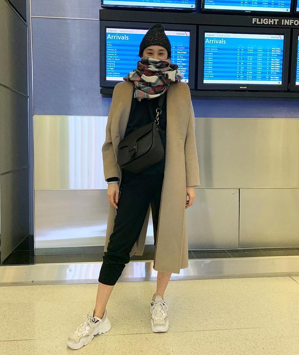 eva chen stands in airport wearing hat, scarf, black sweatsuit, beige coat, and sneakers