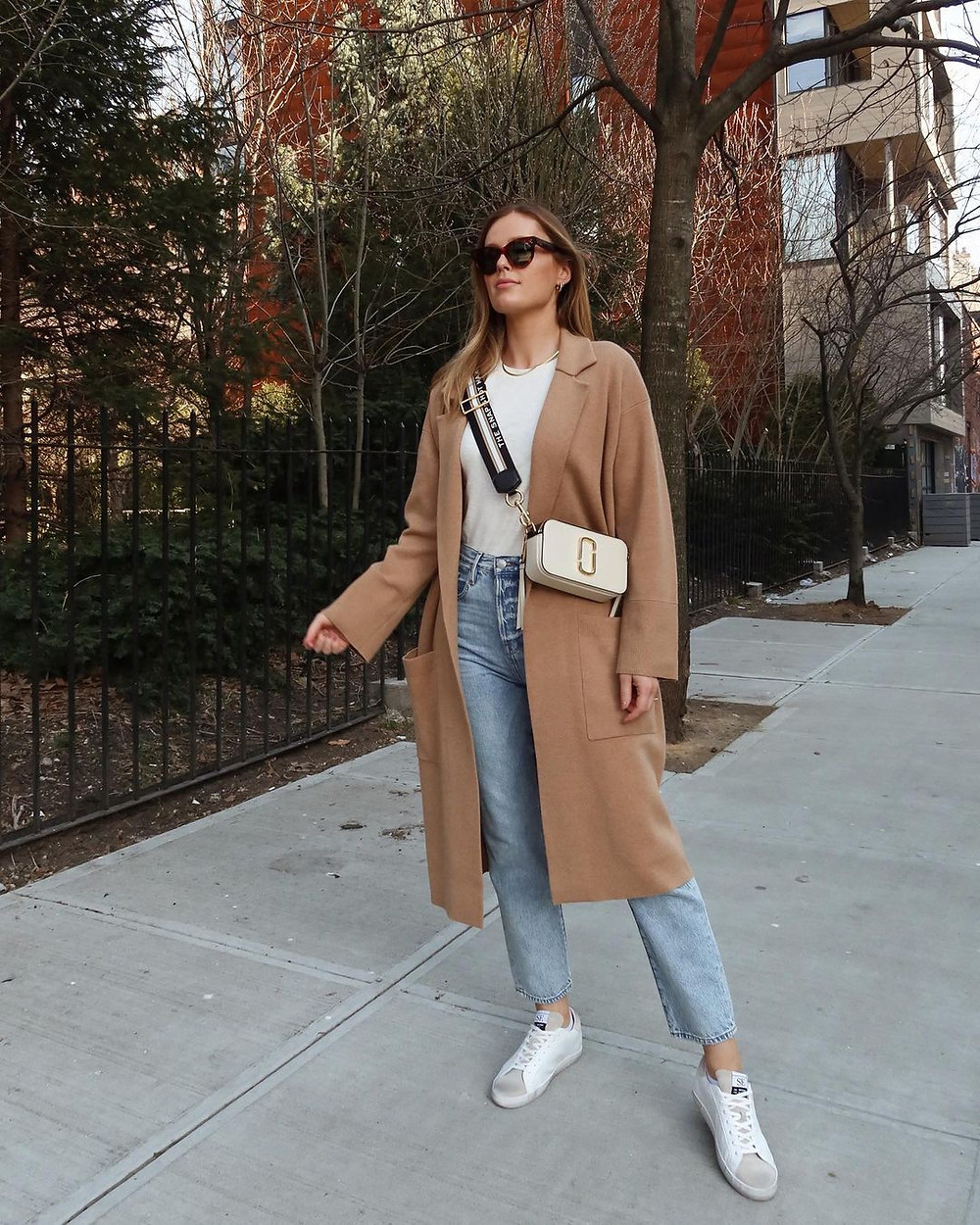 charlotte bridgeman in a camel coat, jeans, t-shirt, crossbody bag, white sneakers and sunglasses in nyc