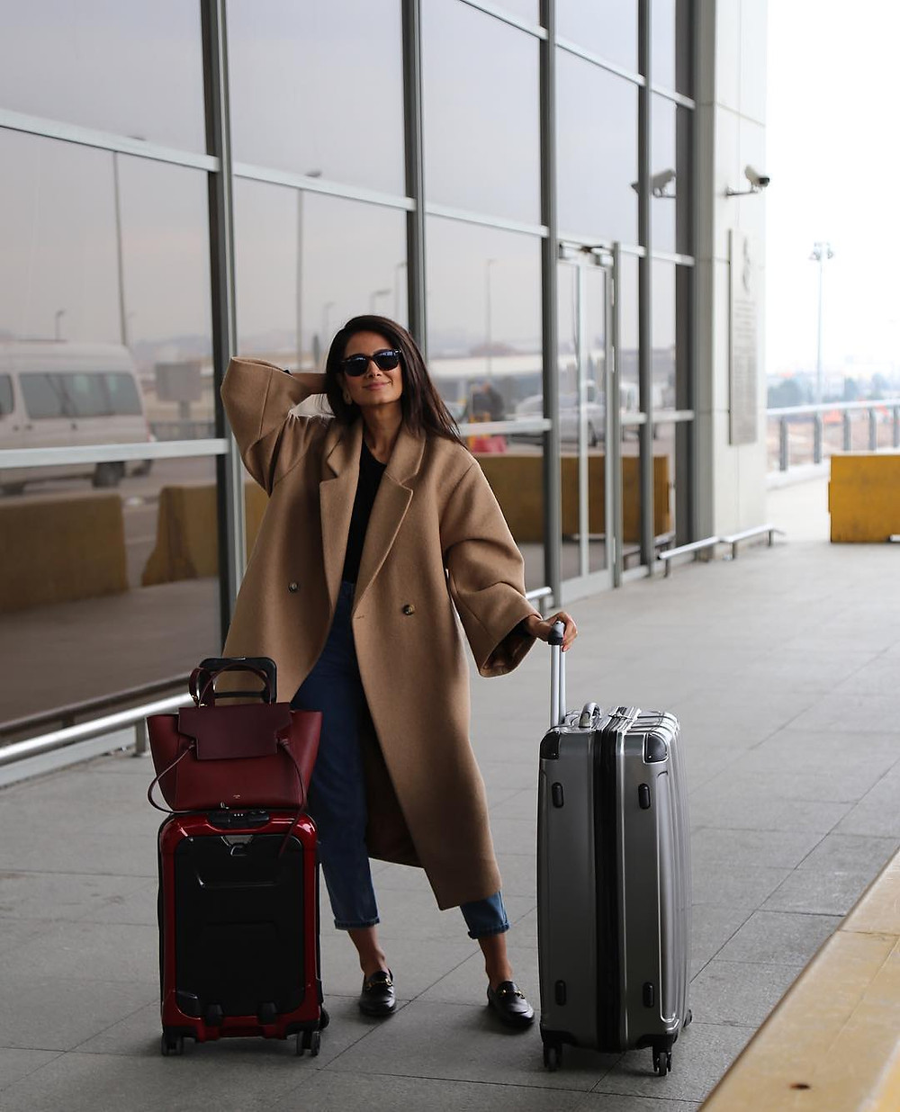 woman wearing camel coat at airport with luggage