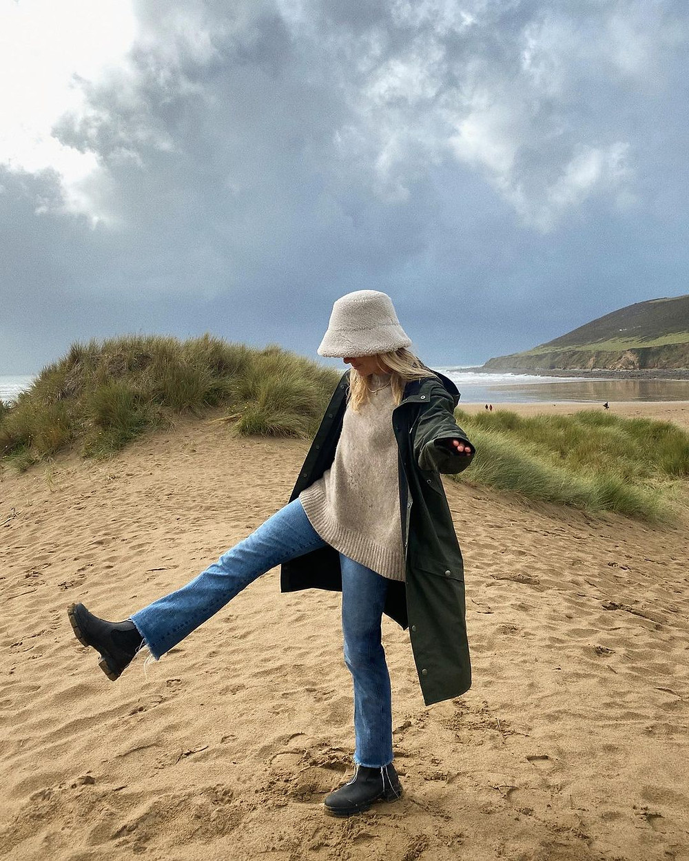 florence pugh wears cute rain boots, jeans, sweater, green jacket, and fuzzy bucket hat while standing on a sandy beach