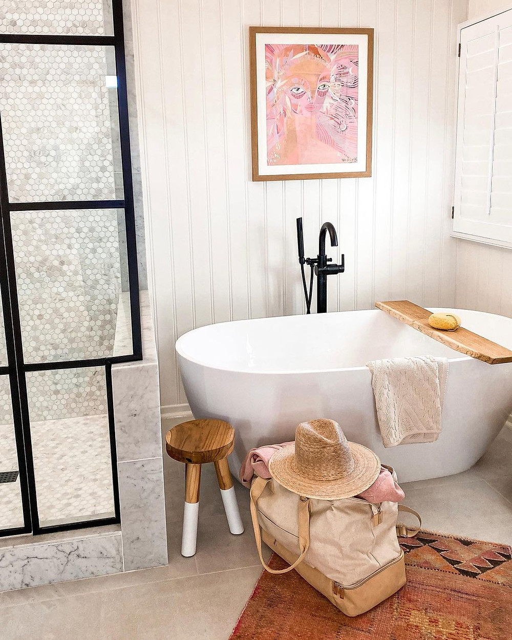 weekender bag sits in front of bathtub in stylish boutique hotel