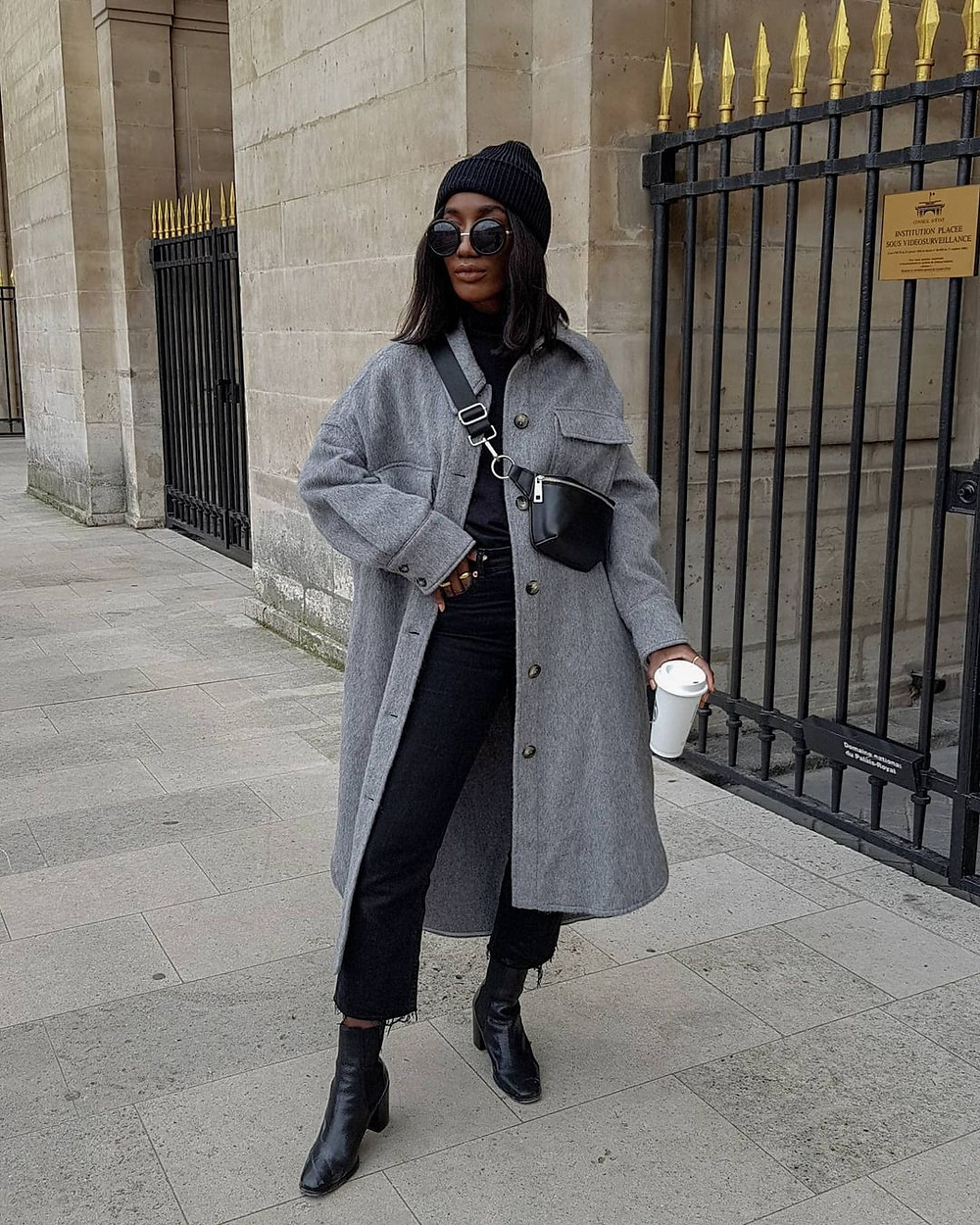 woman wears black leather crossbody bag, grey coat, circular sunglasses, black beanie hat, and black leather boots while standing on the street in front of a stone building with iron gates