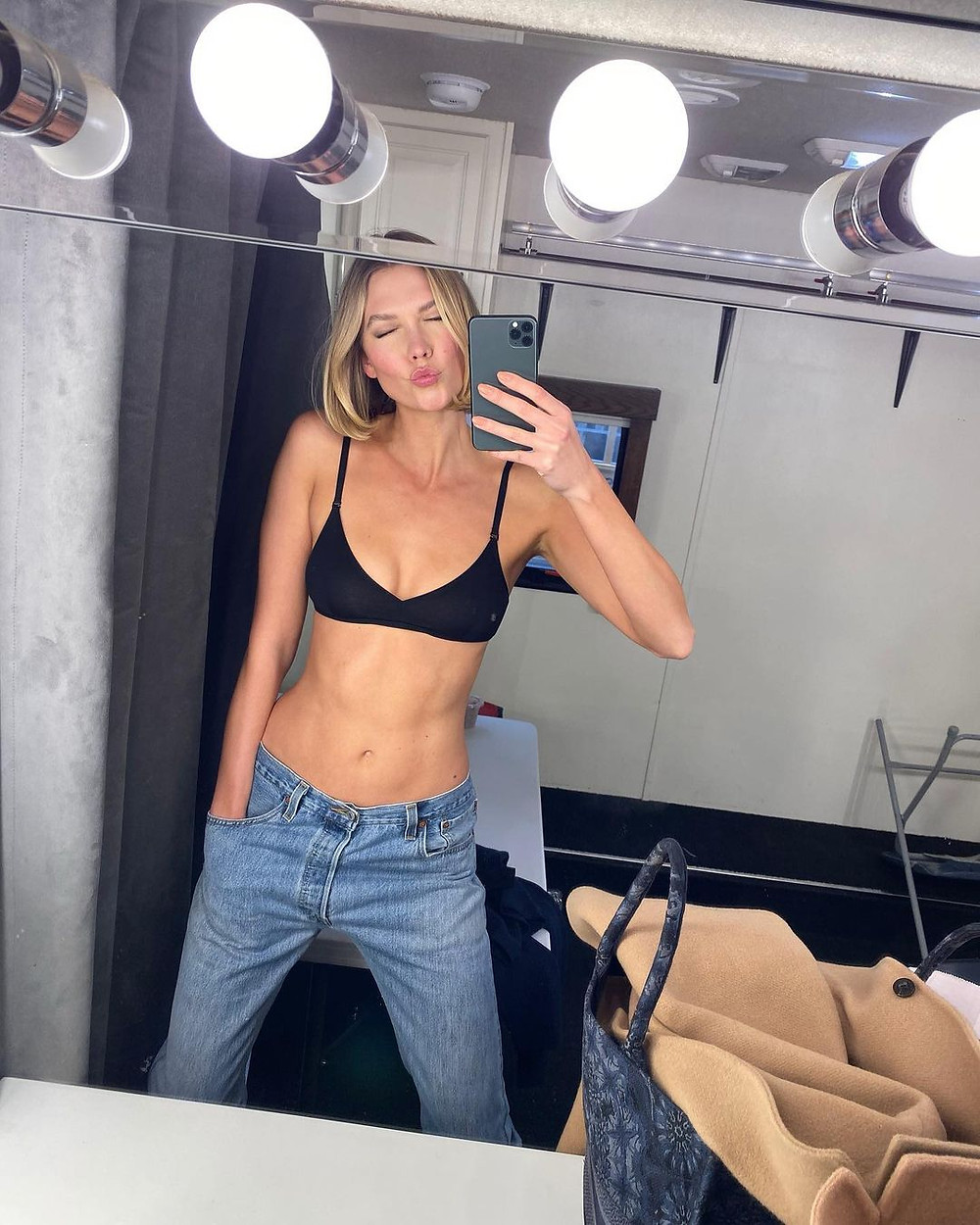 karlie kloss wears the kit undergarments bralette in black and blue jeans while posing for a selfie in front of a mirror