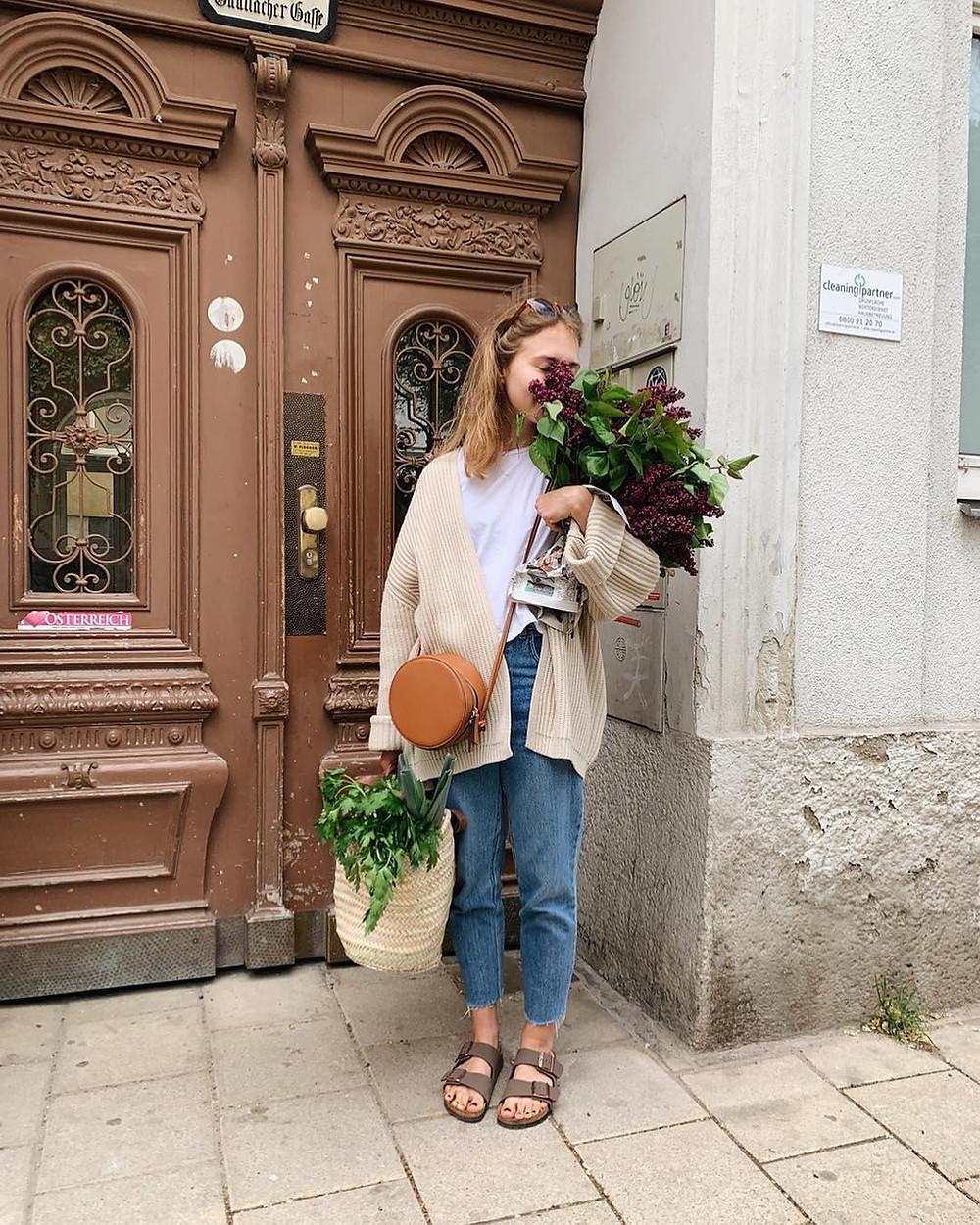 women wears birkenstock sandals while holding flowers