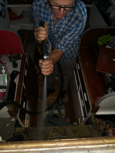 Cleaning the bilge on our wooden sailboat with a fire hose