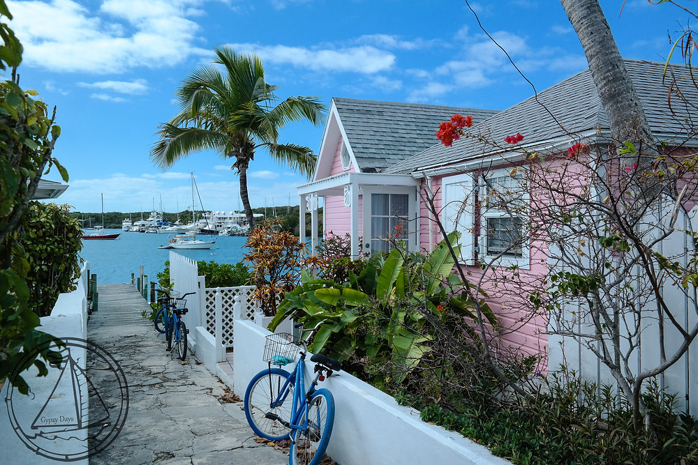 a blue bicycle rests against a white fence in front of a pink house in hope town