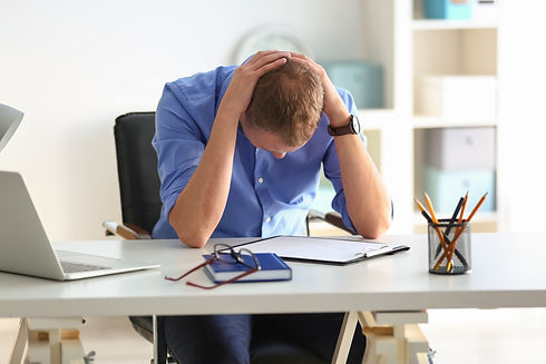Man worried with his hands arond his neck bend over his desk