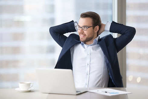 Man in a desk extending his arms and feeling good