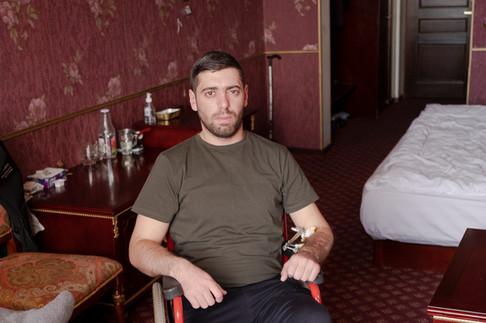 Soldat de 23 ans, Artur a été blessé aux premiers jours des combats : un missile a fait voler en éclats sa maison et la possibilité de se battre. En fauteuil roulant, le bras droit en miettes et la jambe dans le plâtre, il raconte avec amertume comment il s'est retrouvé loin de ses camarades du front.   « Quand j'ai été blessé, on m'a amené à l'hôpital d'Hadrout, ma ville d'origine, puis à Stepanakert, la capitale de l'Artsakh. J'ai été opéré là bas et j'y suis resté dix jours, mais j'avais besoin de plus de soins, alors j'ai été transféré à Erevan pour une deuxième opération », détaille-t-il. Artur vit désormais ici avec son père et sa grand-mère. Il s'ennuie et resasse sans cesse sa déception : « J'ai très mal vécu tout ça. J'étais constamment en contact avec mes amis sur le front et j'avais un gros sentiment de frustration de ne pas participer à cette guerre en tant que militaire »