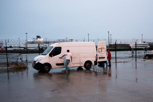 Il est 19 heures, quai Paul Dévot, non loin du centre-ville de Calais. Une camionnette blanche se gare derrière un entrepôt, tandis qu'une pluie battante vient tremper les quelques exilés qui l'attendent. Au loin, on aperçoit ces immenses ferries qui font l'aller-retour entre la France et l'Angleterre. Pour les exilés, nombreux à rêver de passer de l'autre côté de la Manche, la traversée dans l'un de ces navires confortables n'est même pas une option. Il faudra se cacher a l'arrière d'un camion, ou y aller en bateau de fortune, au risque d'y laisser sa vie.