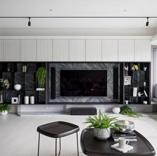 立體皮雕板及義大利進口瓷磚打造的電視牆,錯綜線條,層次豐富。