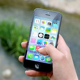 Hand håller i en mobiltelefon