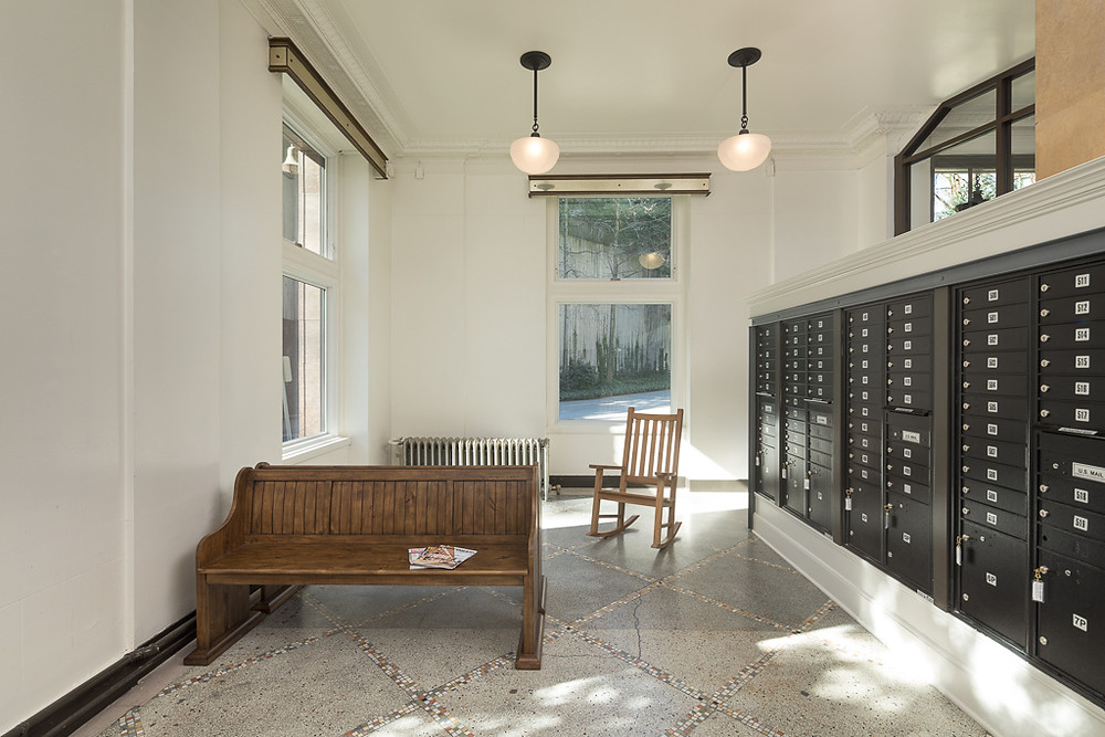 The Cambridge lobby has large windows, white walls, a marble floor. There are resident mailboxes in the center of the space and wooden benches along the left wall.
