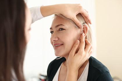 Otolaryngologist putting hearing aid in