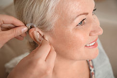 Doctor inserting hearing aid in ear of m