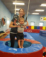 Child and mother playing on gymnastics rings