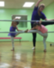 Little girls stretching on ballet bar