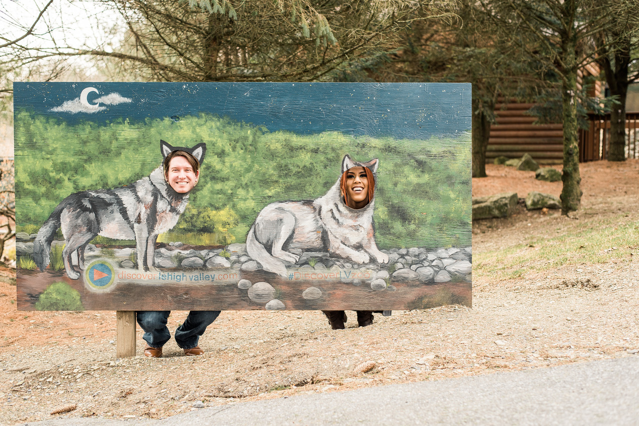 Couple poking their heads through a painted mural in Pennsylvania