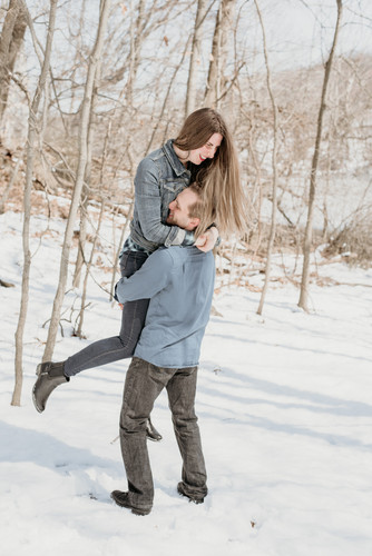 Husband spinning wife in the snow and laughing