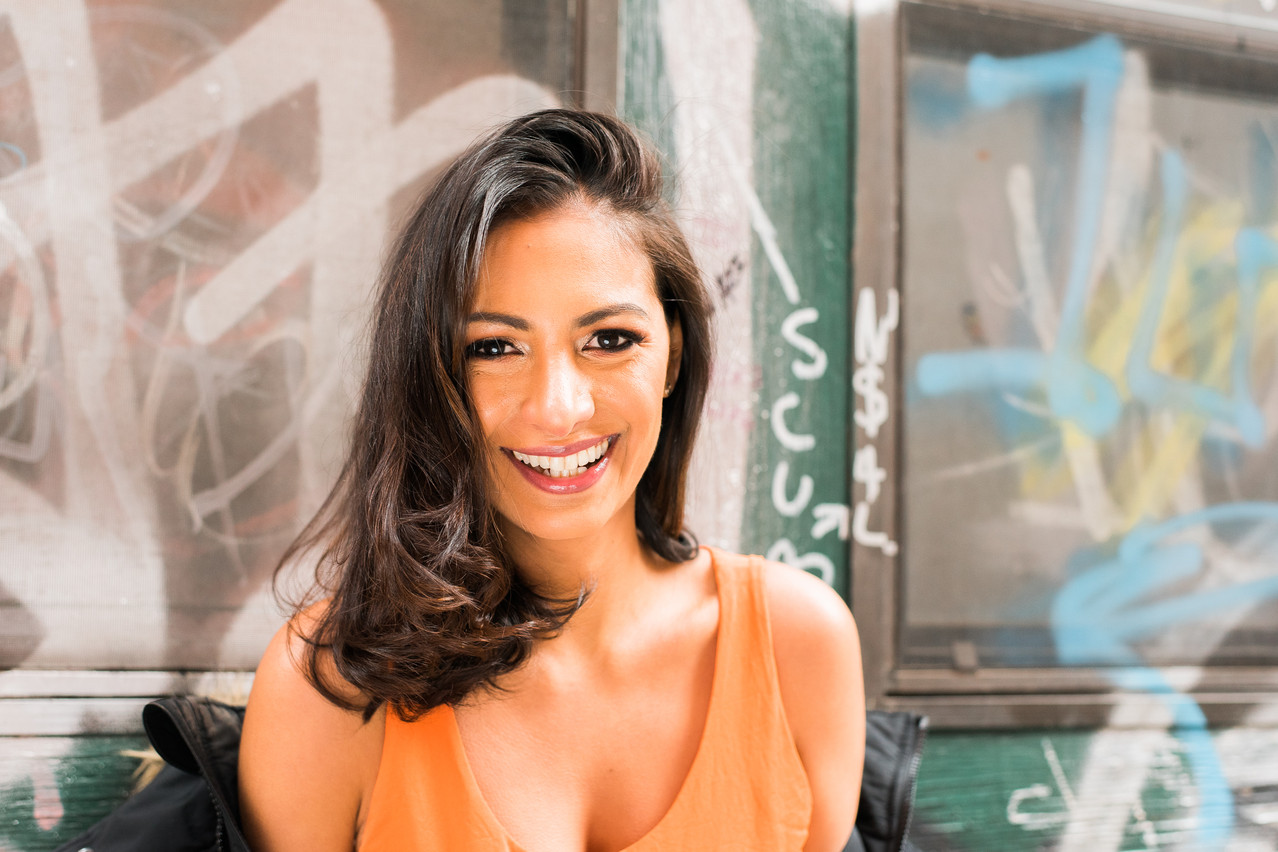 Smiling girl wearing an orange tank top surrounded by graffiti