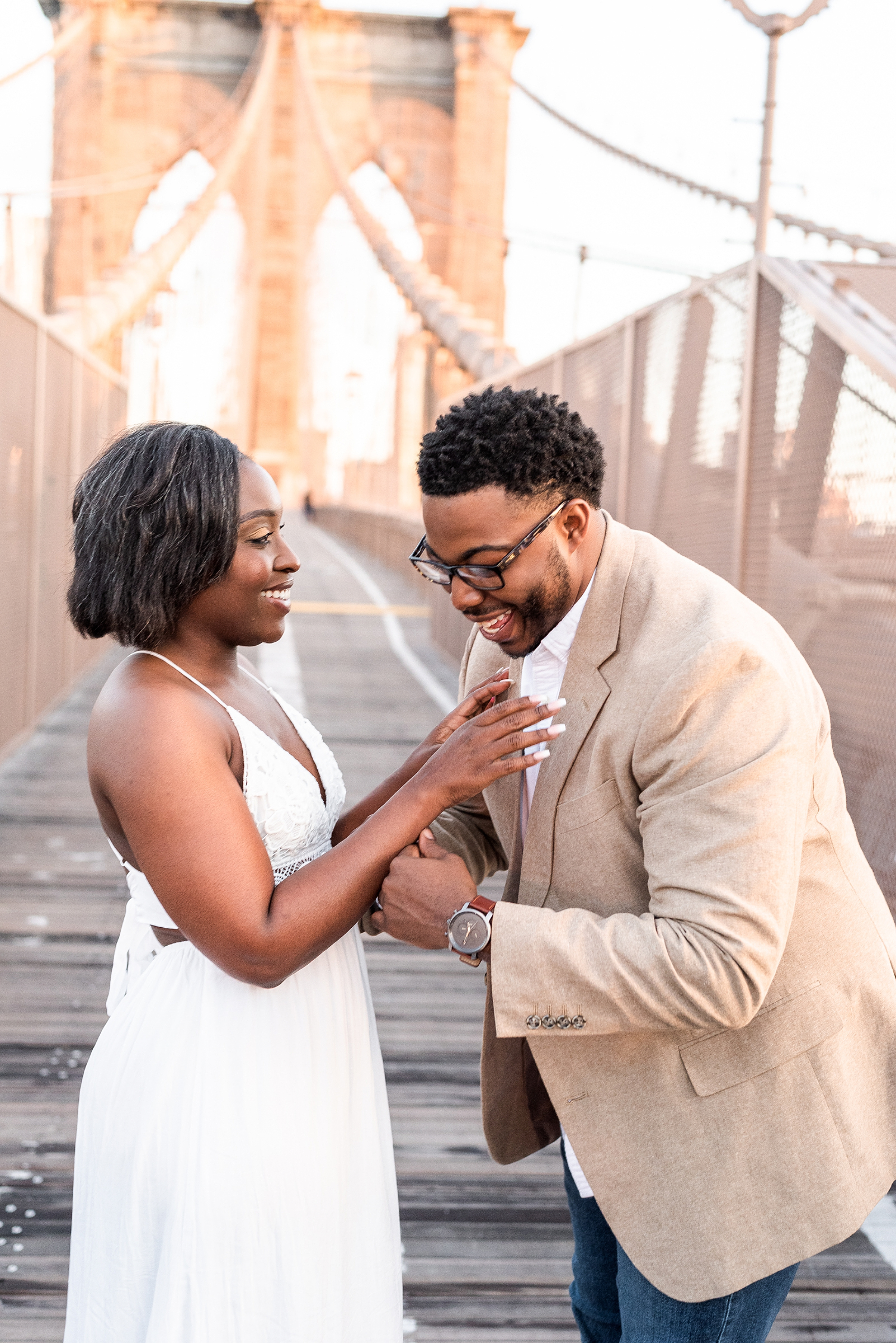 Couple laughing together on the Brooklyn Bridge