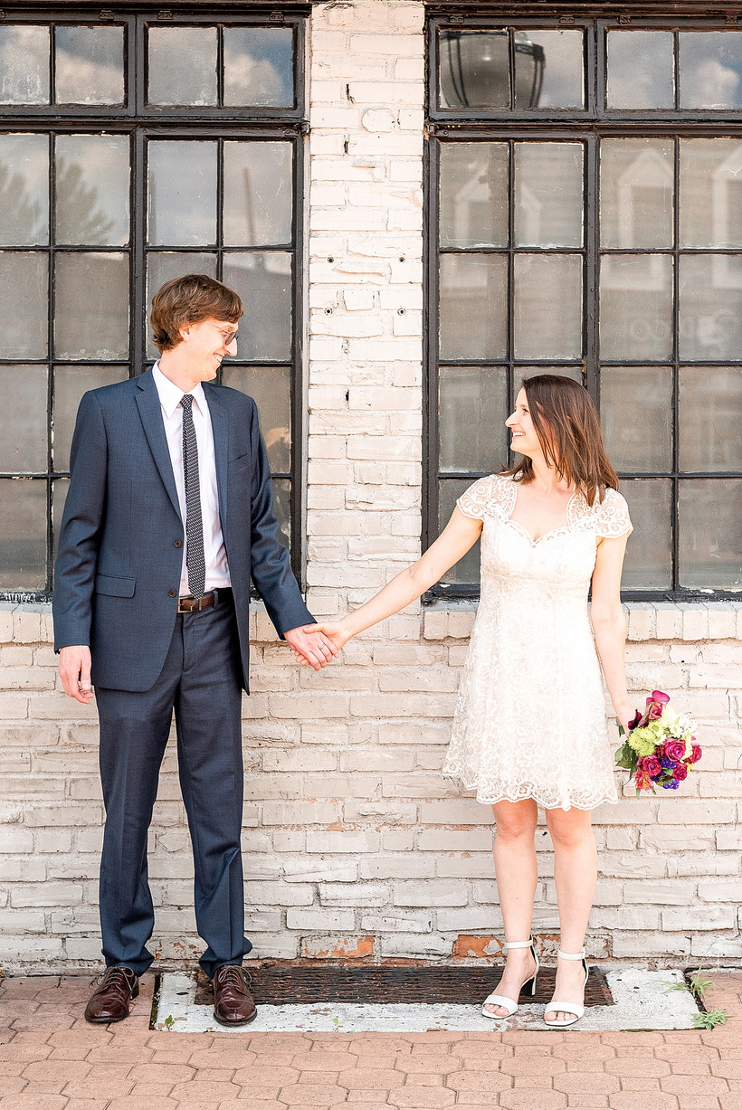 Husband and wife looking at each other and smiling in front of a white brick buiding