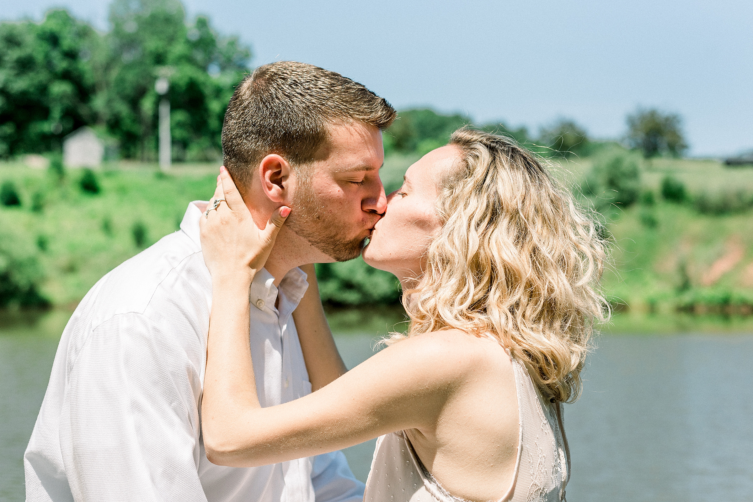 Couple kissing on a dock on a lake