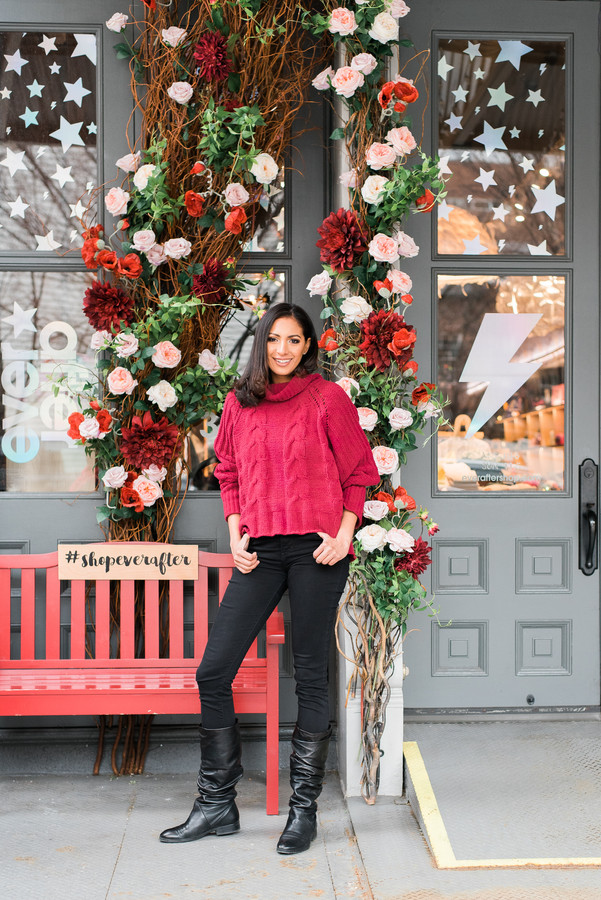 Beautiful woman standing in front of a storefront covered in flowers