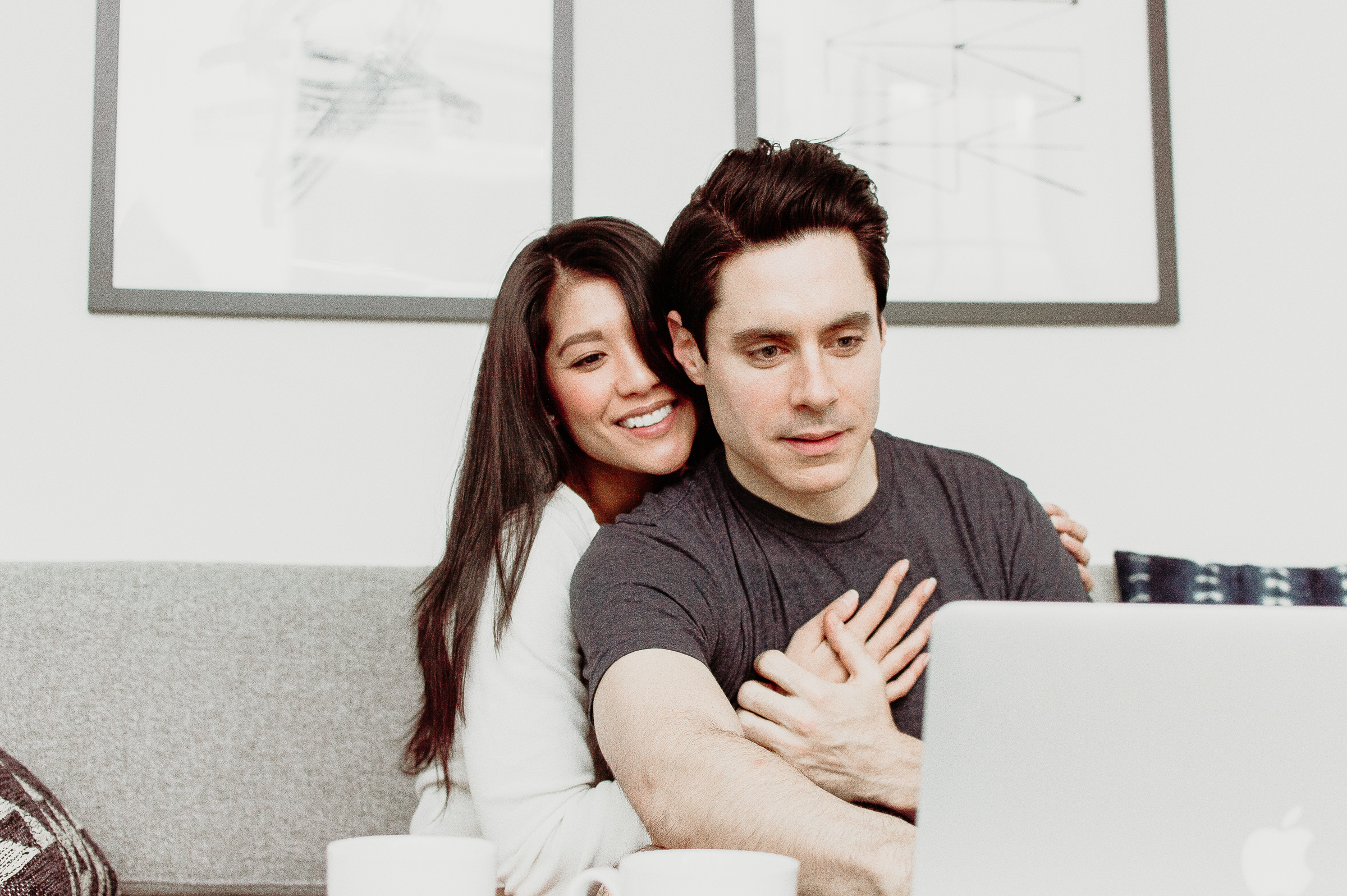 Couple looking at a laptop together on the couch