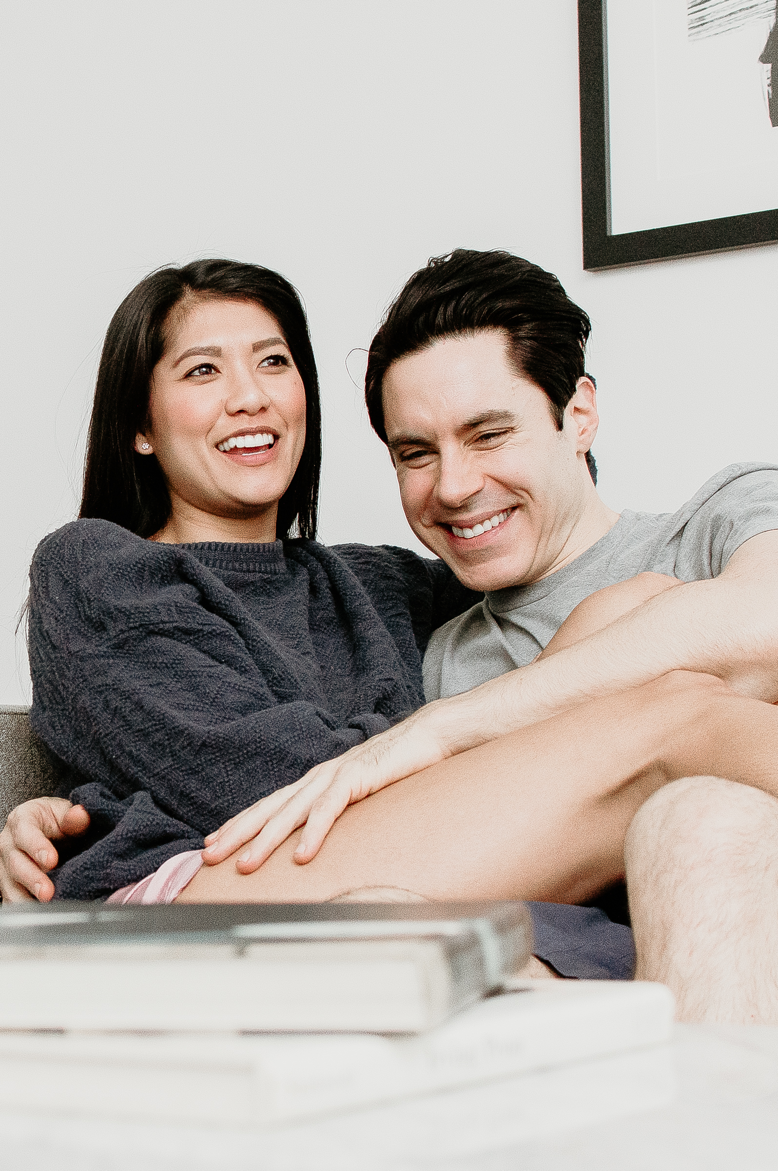 Couple snuggling on the couch together and laughing