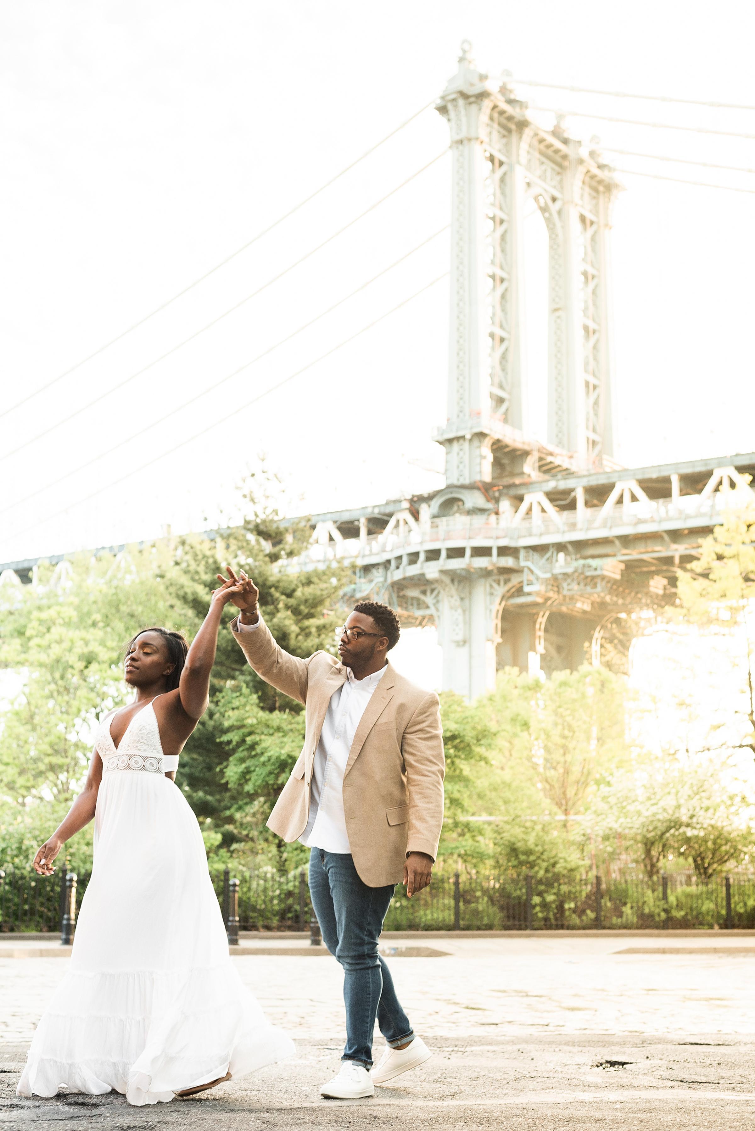 Man twirling his future wife in DUMBO Brooklyn NYC