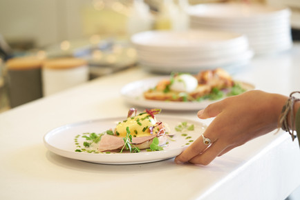 food photography of eggs Benedict plate being lifted by waitress photographed by Naima Maleika