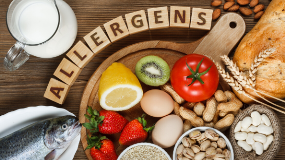 scrabble letters that spell allergens with assortment of foods