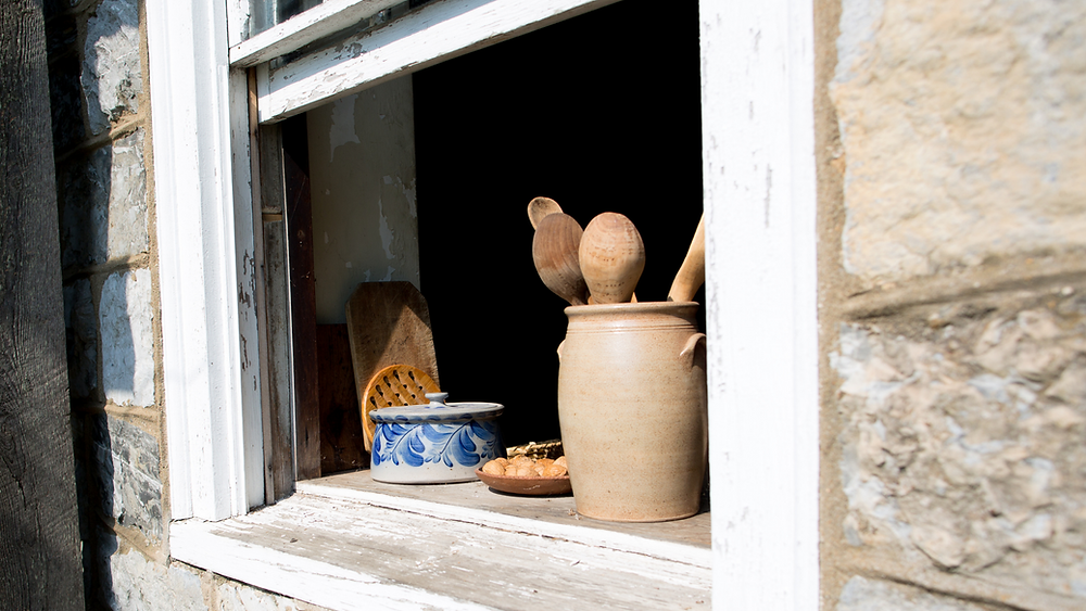 open old window with cooking utensils and bread on ledge