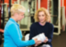 Tina Shiver in gym with client reviewing supplements