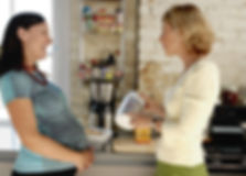 Tina Shiver in kitchen with pregnant client reviewing supplements