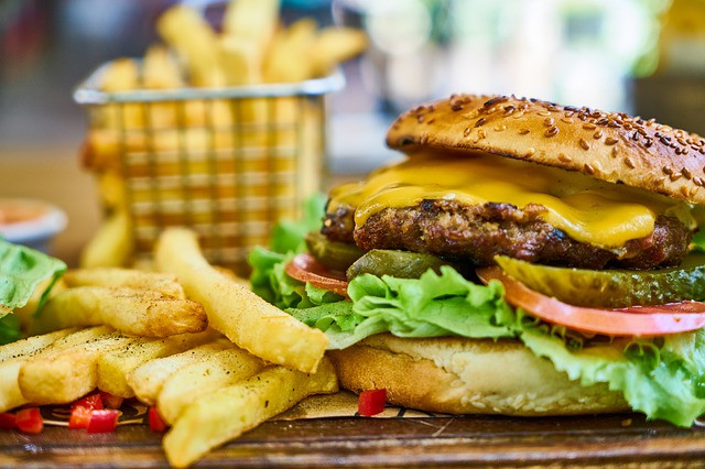 plate with hamburger and fries and basket of fries