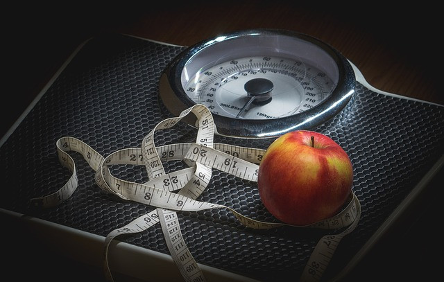 weight scale with a tape measure and apple sitting on it