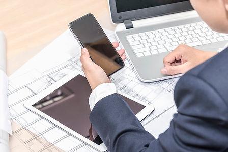 businessman-holding-smartphone-over-tabl