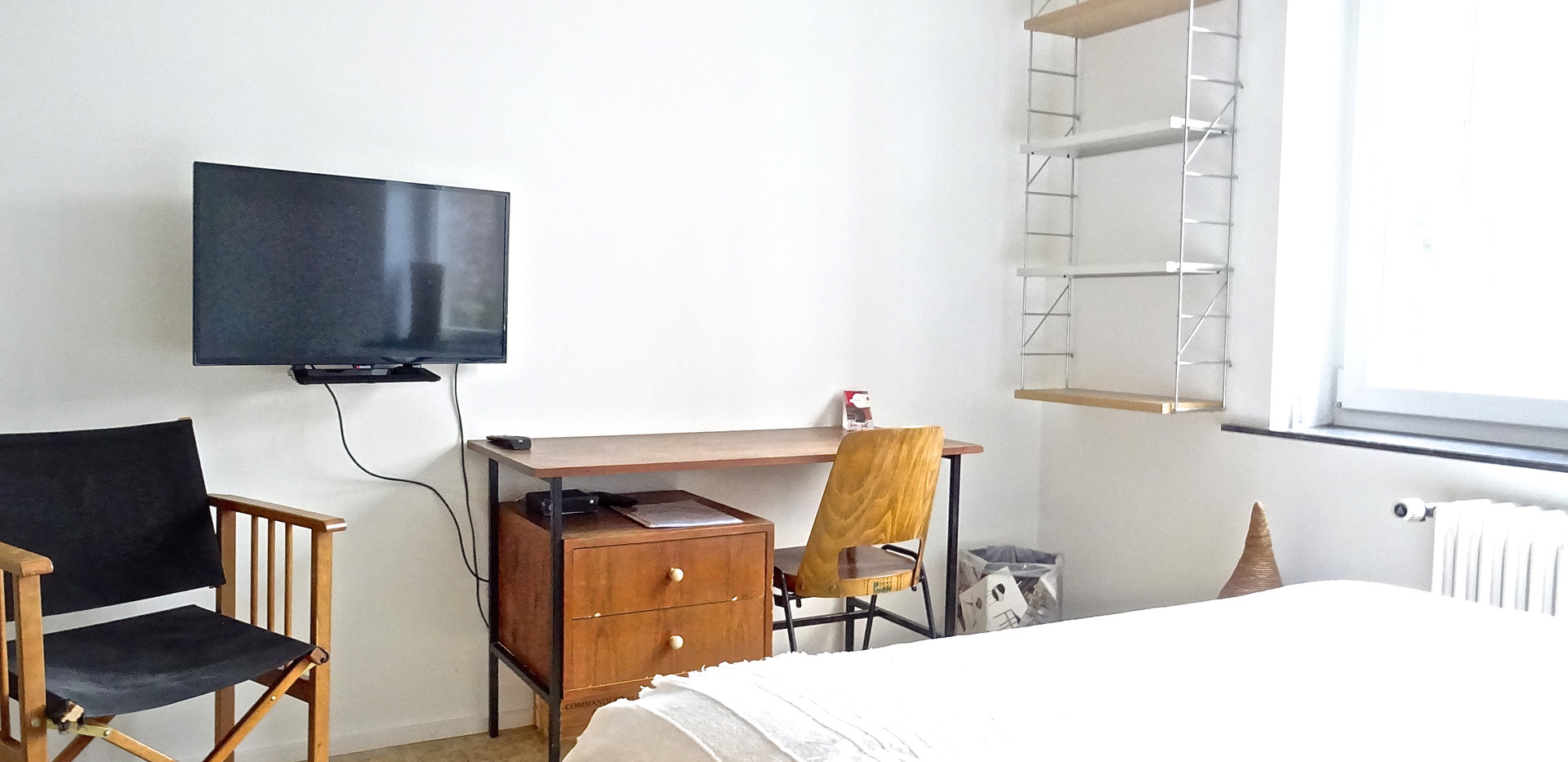 60's bureau table with vintage Baumann chair, Morrocan carpet, african basket & book shelves at White Design Brussels.