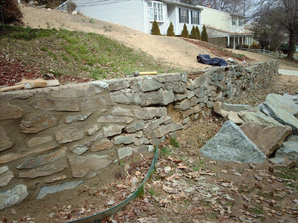 Dinding batu penahan tanah yang rusak termakan waktu. Dinding jenis ini masih membutuhkan perawatan bahkan perbaikan.