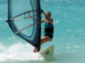 A wind surfer seen from a distance who is a breast cancer survivor and uses a New Attitude breast pr
