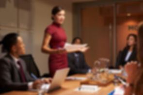 Female manager  standing with documents at business meeting.jpg