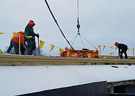 Crane lifting heavy decking from old roof